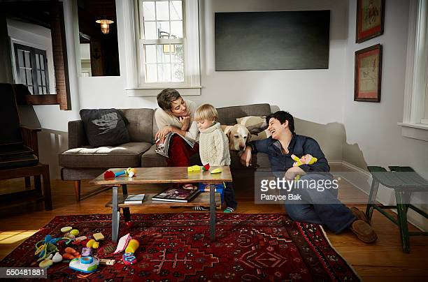 Lesbian moms play w/ their daughter in living room