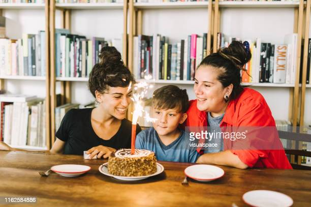 parents lesbiens célébrant l'anniversaire de fils à la maison - couple de jeunes lesbiennes photos et images de collection