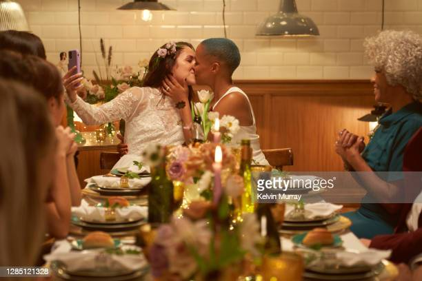 Lesbian wedding party with a friend on a video call