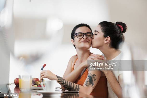 lesbian woman kissing girlfriend at home - lgbtq  female stock pictures, royalty-free photos & images