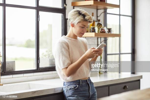 lesbian woman using smart phone in kitchen - three quarter length stock pictures, royalty-free photos & images