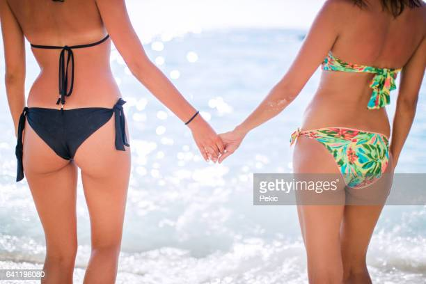 lesbian women on beach holding hands - transgender woman stock photos and pictures