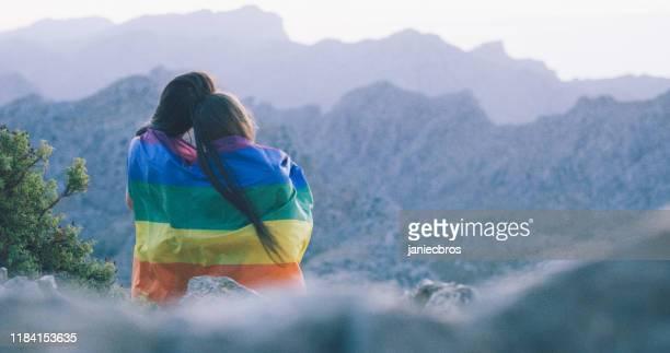 レズビアンは虹の旗で山の上にあります - バイセクシャル ストックフォトと画像