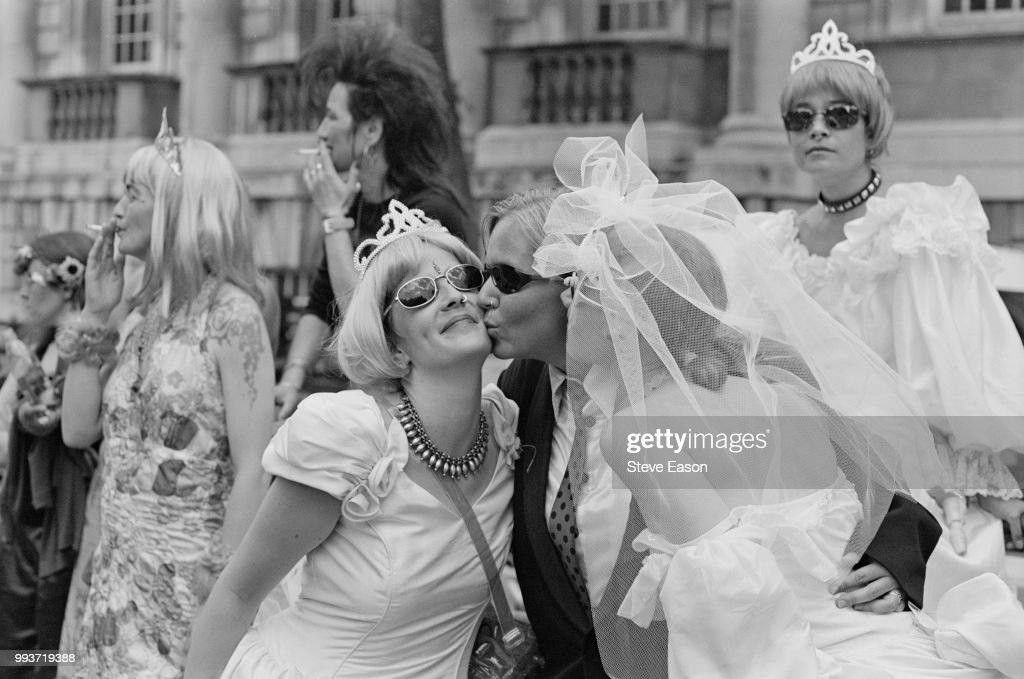 Lesbians in bride, bridesmaid and groom outfits, kissing during the London Mardi Gras, 3rd July 1999. The event was organized by LMG, a consortium of gay and lesbian businesses, which took over after the trust behind the Lesbian and Gay Pride parades became insolvent.
