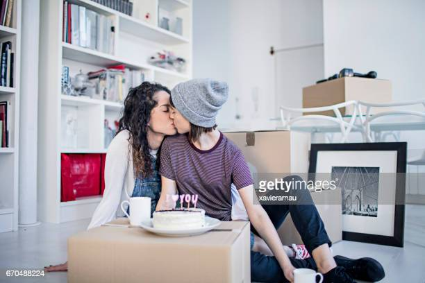 Lesbians kissing by birthday cake at new home