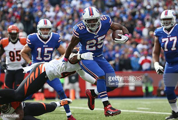 LeSean McCoy of the Buffalo Bills breaks a tackle by George Iloka of the Cincinnati Bengals as he runs with the ball during NFL game action at Ralph...