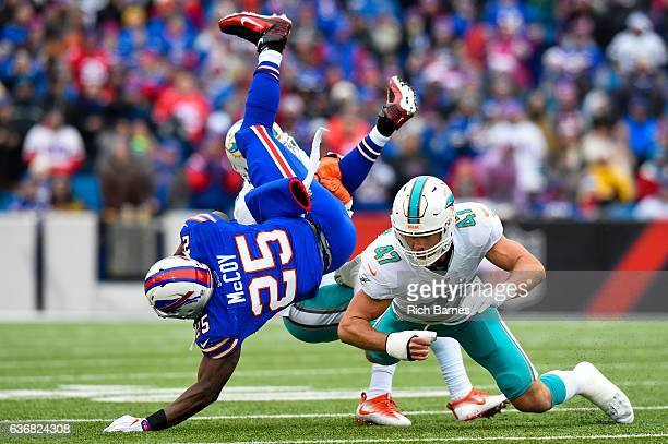LeSean McCoy of the Buffalo Bills is upended while running with the ball by Michael Thomas and Kiko Alonso of the Miami Dolphins during the first...