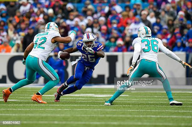 LeSean McCoy of the Buffalo Bills runs with the ball between Spencer Paysinger and Tony Lippett of the Miami Dolphins during the second quarter at...