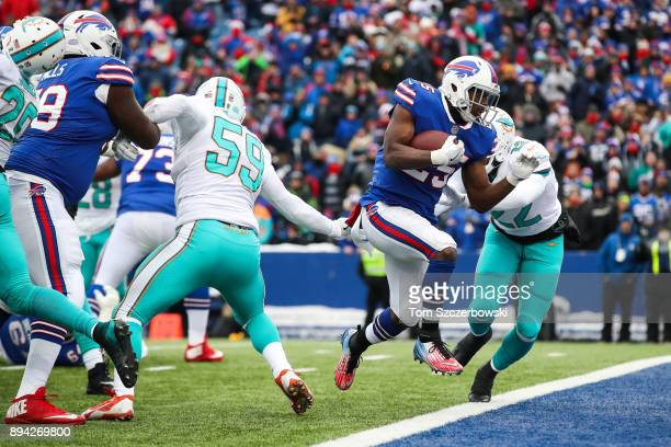LeSean McCoy of the Buffalo Bills scores a touchdown as TJ McDonald of the Miami Dolphins attempts to tackle him during the first quarter on December...