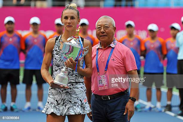 Lesia Tsurenko of Ukraine poses for photographs after winning the final match against Jelena Jankovic of Serbia at the Guangzhou International...