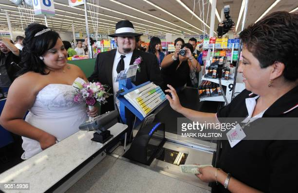 Lesley Barragan and John Tinker pay for their 99 cent wedding ceremony at a checkout at the 99 cent store in Los Angeles on September 9 2009 The...