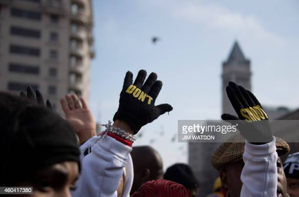 Lesley McSpadden mother of Ferguson shooting victim Michael Brown holds up her hands with gloves that say Don't Shoot during the Justice For All...