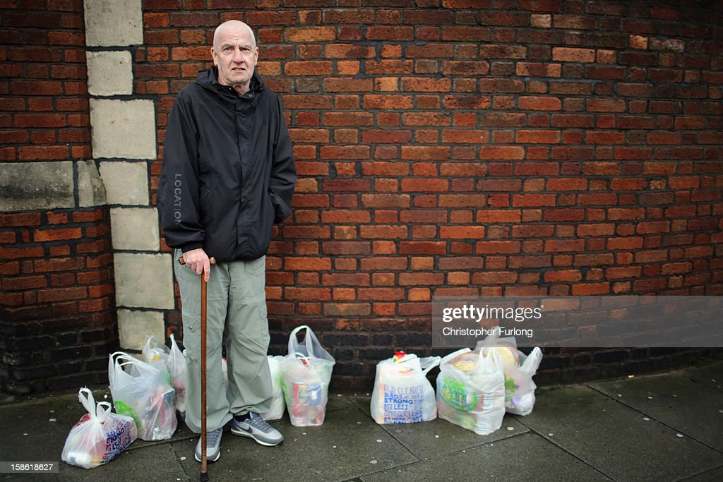 Lesley Stratton stands with bags of food he has received to feed three families over Christmas at Liverpool Central Foodbank on December 21, 2012 in Liverpool, England. With Christmas only days away, volunteers at the Central Liverpool Foodbank at the Frontline Trust, have seen one of their busiest days of the year as they give out free food for the needy. The centre has been giving out festive treats as well as its normal food donation - feeding over 1000 individuals in its first year, including over 300 children.
