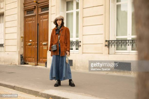 Leslie Bembinster is seen on the street during Paris Fashion Week SS19 wearing vintage suede jacket with baggy jeans black heels and large hat on...