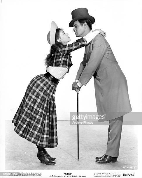 Leslie Caron and Louis Jourdan leaning into each other for a kiss in publicity portrait for the film 'Gigi' 1958