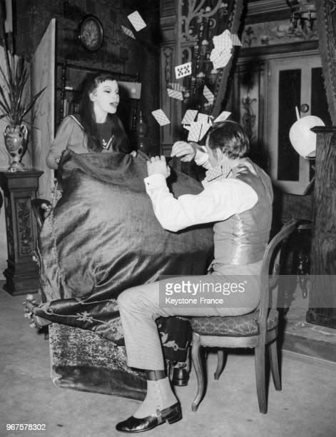 Leslie Caron et Tony Britton dans une scène de jeux de cartes dans la pièce 'Gigi' sur la scène du New Theatre à Londres, Royaume-Uni le 22 mai 1956.