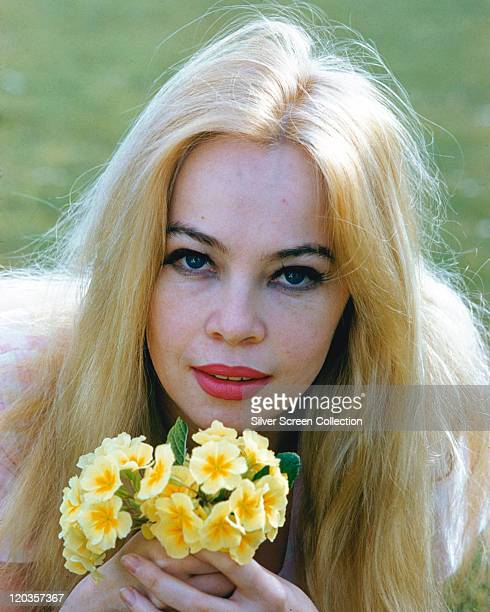 Leslie Caron, French actress, poses with long blonde hair, holding a posy of yellow flowers, circa 1965.