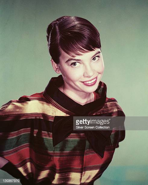 Leslie Caron, French actress, smiling while posing in a top with multi-coloured horizontal stripes and a black bow attached to the front, circa 1960.