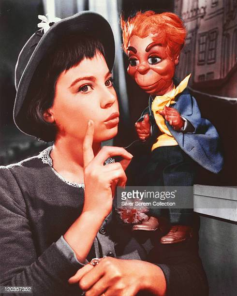 Leslie Caron French actress wearing a grey jacket and matching hat posing beside a puppet in a publicity still issued for the film 'Gigi' 1958 The...