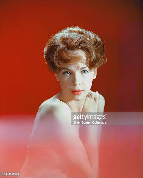 Leslie Caron, French actress, with bare shoulders with lower half of the image out of focus, posing in a studio portrait, against a red background,...