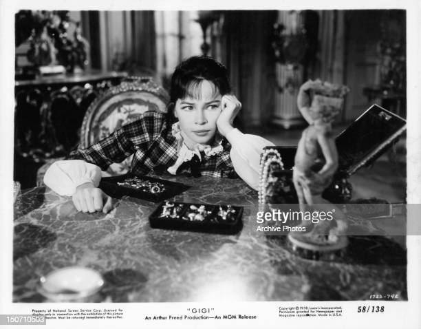 Leslie Caron sitting before jewel boxes in a scene from the film 'Gigi' 1958