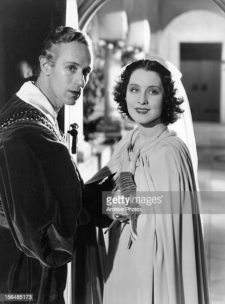 Leslie Howard stands beside Norma Shearer in a scene from the film 'Romeo And Juliet' 1936