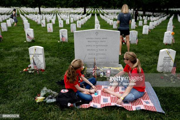 Leslie HufstedlerAlverez and her daughter Grace Hufstedler sit at the grave of Lt Doyle Hufstedler at Arlington National Cemetery in Arlington...