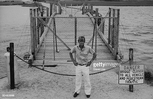 Leslie Leland standing in front of the nowclosed Dike Bridge w danger sign in front of it Leland was foreman of the Grand Jury that considered the...