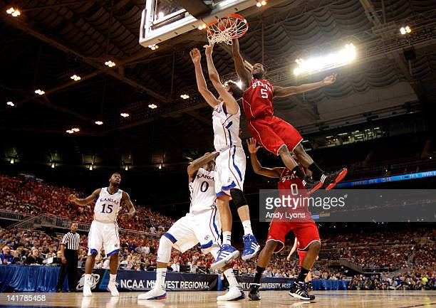 J Leslie of the North Carolina State Wolfpack attempts to dunk a put back shot on a rebound in the first half against Jeff Withey of the Kansas...
