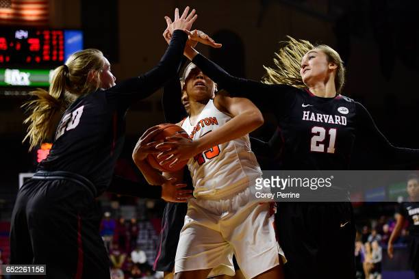 Leslie Robinson of the Princeton Tigers is guarded by Madeline Raster and Taylor Finley of the Harvard Crimson during the third quarter of an Ivy...