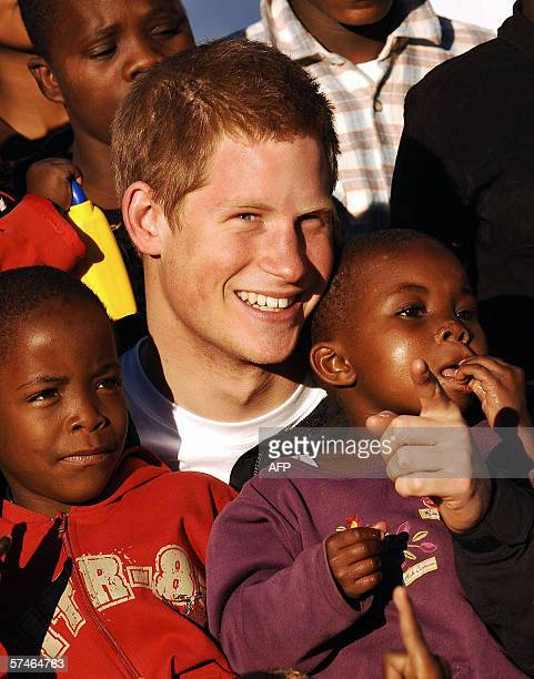 Britain's Prince Harry cuddles children Mutsu and Lintle in the grounds of the Mants'ase children's home 24 April 2006 while on a return visit to...