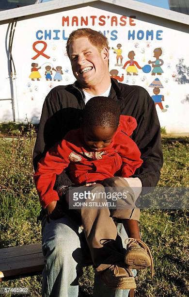 Britain's Prince Harry giggles as he holds old friend Mutsu Potsane in the grounds of the Mants'ase childrens home during a return visit to Lesotho...