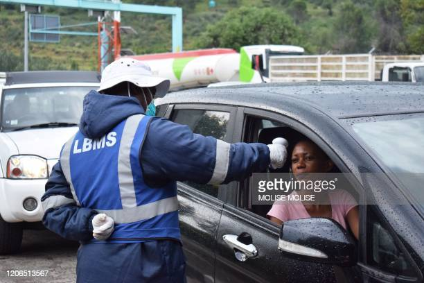 A Lesotho health official measures temperatures of motorists as a preventive measure against the spread of the COVID19 coronavirus at the Maseru...