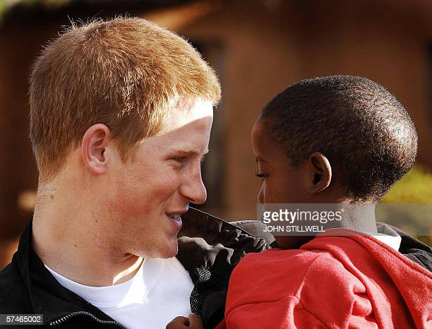 Britain's Prince Harry meets his old friend Mutsu Potsane in the grounds of Mants'ase children's home 24 April 2006 while on a return visit to...