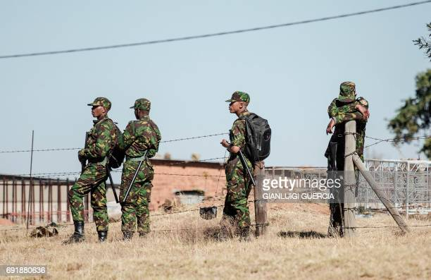 Lesotho soldiers stand close to a voting station during the country's general elections on June 3 in Maseru. Lesotho is holding elections on June 3,...