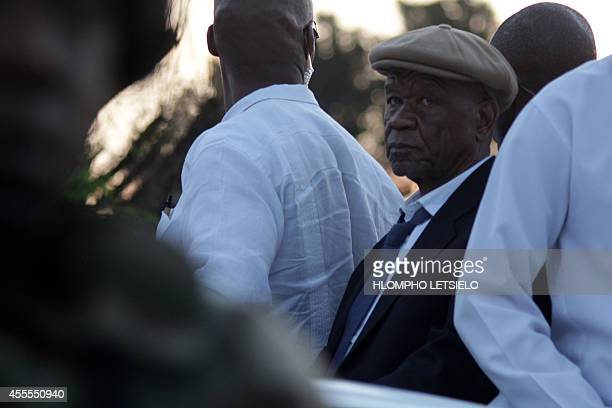 Lesotho's Prime Minister Tom Thabane is flanked by his bodyguards as he arrives at Maseru border gate under heavy security on September 16, 2014....