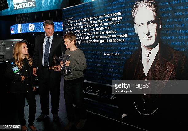 Lester Patrick Trophy honoree Cam Neely chats with his son Jack and daughter Ava after he received his trophy during a Celebration of Lester Patrick...