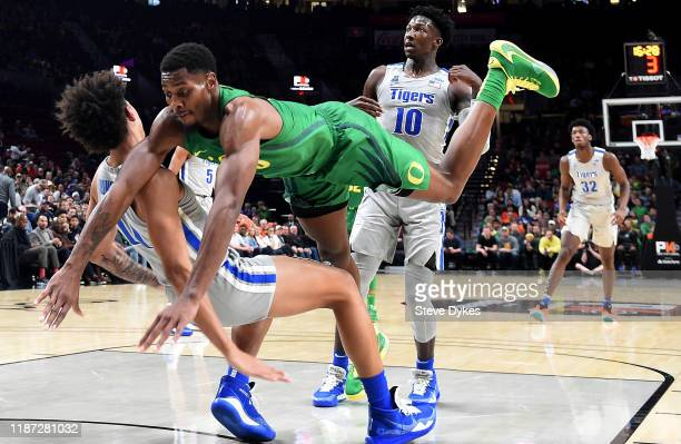 Lester Quinones of the Memphis Tigers takes a charging foul on Shakur Juiston of the Oregon Ducks as Damion Baugh of the Memphis Tigers looks on...