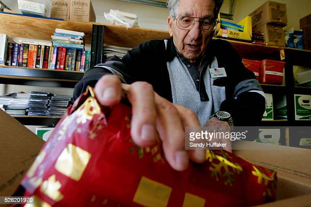 Lester Tenney loads a care package to be sent to troops overseas in a garage at the La Costa Glen Retirement Community where they live on Monday...