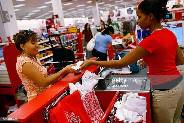 Leticia Cam receives her change from Target cashier Candace Collier on December 16 2008 in Miami Florida The government announced today that consumer...