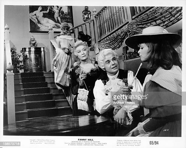 Leticia Roman watches as man aims scratcher at Miriam Hopkins' chin in a scene from the film 'Fanny Hill Memoirs of a Woman of Pleasure' 1964