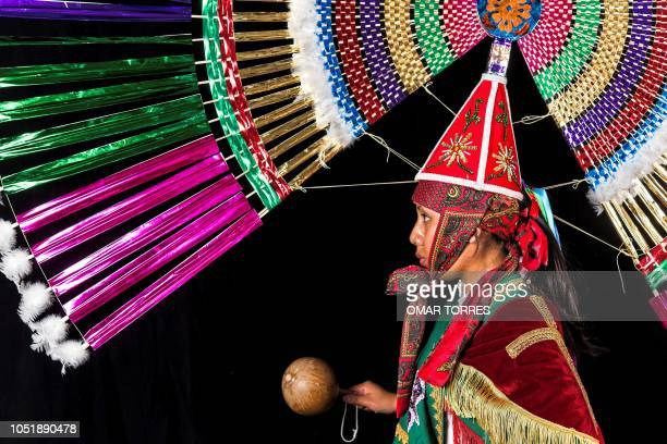 TOPSHOT Leticia Uribe Hernandez poses for a photograph with her traditional costume during the presentation of the Huey Atlixcayotl Festival on...