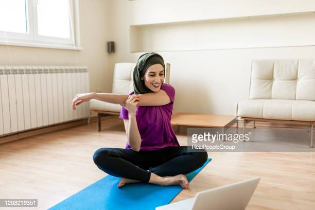 let's burn that belly fat with a home workout session. a muslim woman is doing yoga at home with online help - home workout stock pictures, royalty-free photos & images