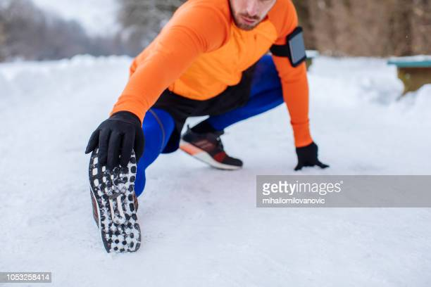 man snow stretching after running park