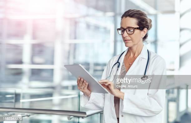 laten we eens kijken naar de toelichting van de verpleegster links op mijn patiënt... - vrouwelijke dokter stockfoto's en -beelden
