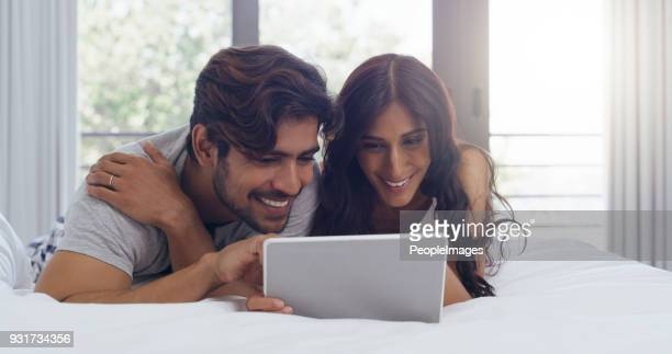 let's spend the entire day in bed watching shows - indian couples stock pictures, royalty-free photos & images