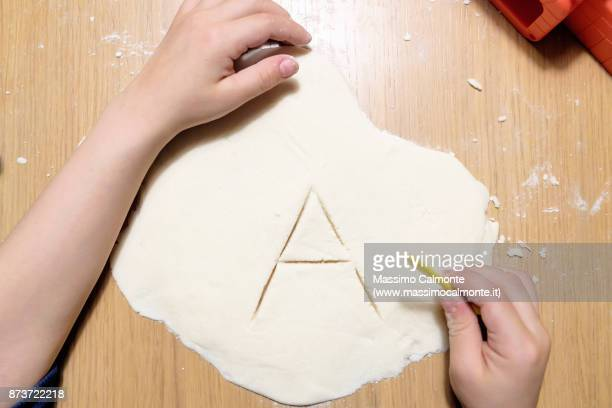 Letter A engraved on the salt paste by a child on a wooden table
