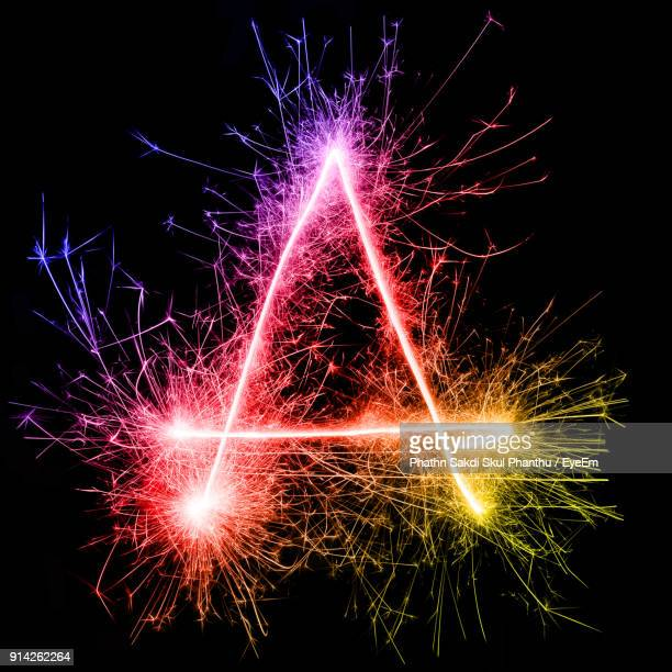 letter a made by multi colored sparklers at night - letter a stock pictures, royalty-free photos & images