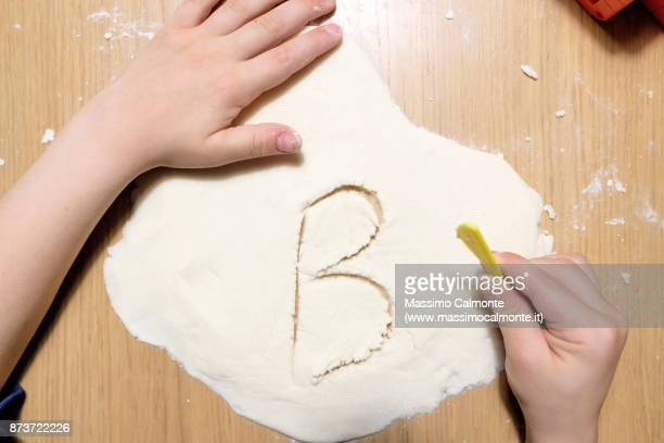 Letter B engraved on the salt paste by a child on a wooden table