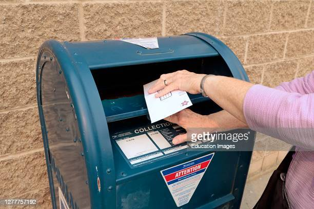 Letter being inserted into United States Postal Service blue box.